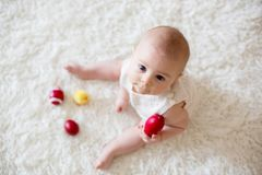 Cute little toddler baby boy, playing with colorful easter eggs Stock Photos