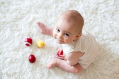 Cute little toddler baby boy, playing with colorful easter eggs. And little decorative ducks, isolated shot, beige background Stock Photo