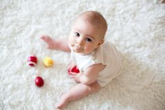 Cute little toddler baby boy, playing with colorful easter eggs. And little decorative ducks,  shot, beige background Stock Photo