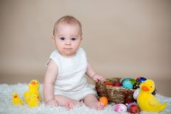 Cute little toddler baby boy, playing with colorful easter eggs. And little decorative ducks,  shot, beige background Royalty Free Stock Photography