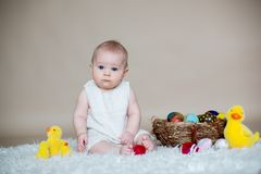 Cute little toddler baby boy, playing with colorful easter eggs. And little decorative ducks,  shot, beige background Royalty Free Stock Photos
