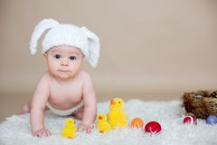 Cute little toddler baby boy, playing with colorful easter eggs. And little decorative ducks,  shot, beige background Stock Images