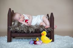 Cute little toddler baby boy, sleeping with colorful easter eggs Stock Image