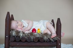 Cute little toddler baby boy, sleeping with colorful easter eggs. And little decorative ducks,  shot, beige background Royalty Free Stock Photos