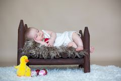 Cute little toddler baby boy, sleeping with colorful easter eggs. And little decorative ducks,  shot, beige background Stock Photo