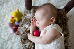Cute little toddler baby boy, sleeping with colorful easter eggs. And little decorative ducks,  shot, beige background Royalty Free Stock Photography
