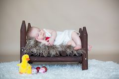 Cute little toddler baby boy, sleeping with colorful easter eggs. And little decorative ducks,  shot, beige background Stock Image