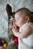 Cute little toddler baby boy, sleeping with colorful easter eggs. And little decorative ducks,  shot, beige background Royalty Free Stock Photo