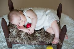 Cute little toddler baby boy, sleeping with colorful easter eggs. And little decorative ducks,  shot, beige background Stock Photos