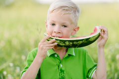 Cute little toddler boy with blond hairs eating watermelon in summergarden Royalty Free Stock Images