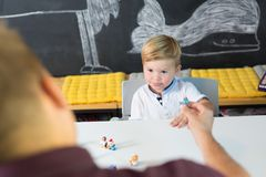 Cute little toddler boy at child therapy session. Cute little playfull toddler boy at child therapy session. Private one on one homeschooling with didactic aids Stock Photos
