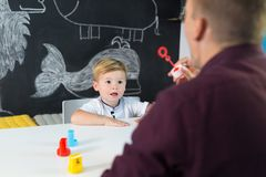 Cute little toddler boy at child therapy session. Cute little playfull toddler boy at speech therapy session. Private one on one homeschooling with didactic Royalty Free Stock Photo