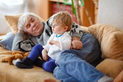Cute little toddler boy and grandfather watching together tv show. Baby grandson and happy retired senior man sitting stock photo