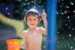 Cute little toddler boy, having fun with splashed water shot dur Royalty Free Stock Image