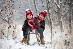 Cute little toddler boy and his older brothers, playing outdoors with snow on a winter day. Snowing royalty free stock images