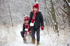 Cute little toddler boy and his older brothers, playing outdoors with snow on a winter day. Snowing stock image