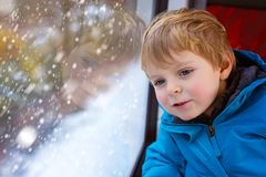 Cute little toddler boy looking out train window Stock Image