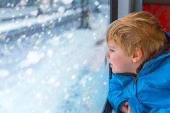 Cute little toddler boy looking out train window Stock Images