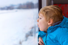 Cute little toddler boy looking out train window Royalty Free Stock Photo