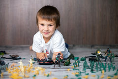 Cute little toddler boy, playing at home with soldiers and figur Royalty Free Stock Photography
