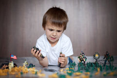 Cute little toddler boy, playing at home with soldiers and figur Stock Photos