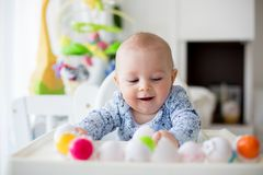 Cute little toddler boy, playing with plastic eggs, sitting in a royalty free stock images
