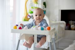 Cute little toddler boy, playing with plastic eggs, sitting in a Royalty Free Stock Photos