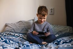 Cute little toddler boy playing with a smartphone on the bed. Internet dependence concept stock photos