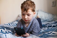 Cute little toddler boy playing with a smartphone on the bed. Internet dependence concept stock photography