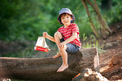 Cute little toddler boy, playing with wooden boat on a pond Stock Photo