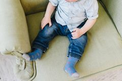 Cute little toddler boy sitting in armchair stock photo
