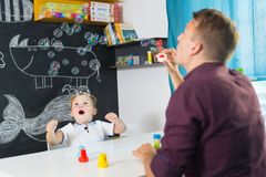 Cute little toddler boy at speechtherapist session. Cute little playfull toddler boy amazed by milky bubbles at child therapy session. Private one on one Stock Images