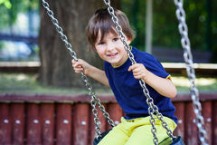 Cute little toddler boy, swinging in the park, summertime Stock Photo