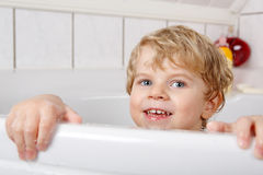 Cute little toddler boy of two years having fun by taking bath i Stock Image