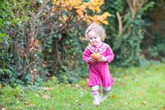 Cute little toddler girl with apple in autumn garden Stock Image