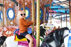 Cute Little Toddler Girl in Big Sunglasses Riding on Carnival Ca. A cute llittle toddler girl in big fashionable sunglasses is riding on a classic carousal horse royalty free stock image