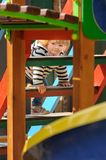 Cute little toddler girl climbing stairs of a children`s slide stock photo
