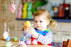 Cute little toddler girl decorating tree bough with colored pastel plastic eggs. Happy baby child having fun with Easter. Decorations. Adorable healthy smiling royalty free stock image