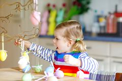 Cute little toddler girl decorating tree bough with colored pastel plastic eggs. Happy baby child having fun with Easter. Decorations. Adorable healthy smiling stock image