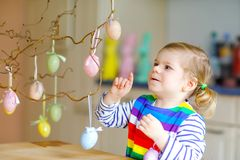 Cute little toddler girl decorating tree bough with colored pastel plastic eggs. Happy baby child having fun with Easter. Decorations. Adorable healthy smiling royalty free stock photos