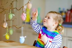 Cute little toddler girl decorating tree bough with colored pastel plastic eggs. Happy baby child having fun with Easter. Decorations. Adorable healthy smiling royalty free stock photography