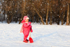 Cute little toddler girl dig in winter snow Stock Image
