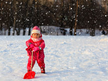 Cute little toddler girl dig winter snow. Cute little toddler girl dig in winter snow, kids winter fun royalty free stock photography