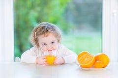 Cute little toddler girl drinking orange juice Stock Photos
