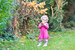 Cute little toddler girl eating apple in garden Royalty Free Stock Photo