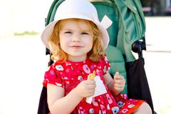 Cute little toddler girl eating ice cream in cone on family vacations. Happy healthy baby child with icecream waffle royalty free stock images
