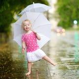 Cute little toddler girl having fun under a rain