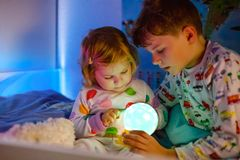 Cute little toddler girl and kid boy playing with colorful night light lamp before going to bed. Sleepy tired baby. Sister and brother in nightwear having fun royalty free stock images