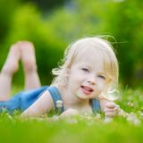Cute little toddler girl laying in the grass Stock Image