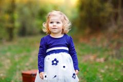 Cute little toddler girl making a walk through autumn park. Happy healthy baby enjoying walking with parents. Sunny warm royalty free stock photography